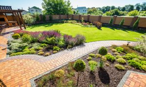 bricBrick paver walkways and patio accent a beautifully landscaped back yard