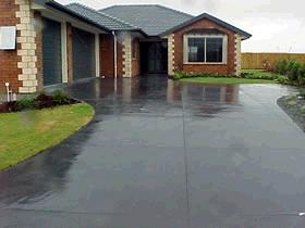 Concrete driveway colored to match the garage doors and roof