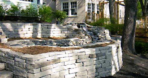 Terraced and curved stacked-stone retaining walls with water feature in Boulder