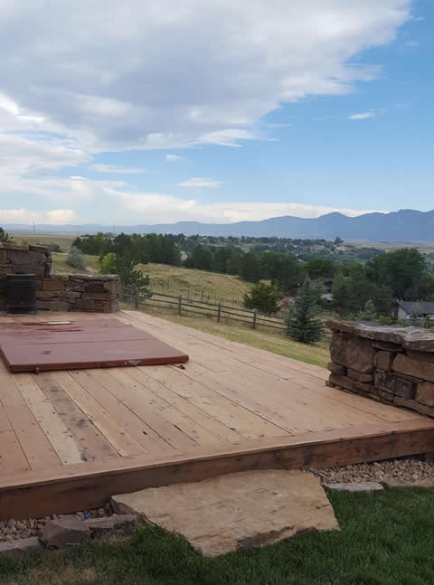 Rustic deck with stacked-stone wall hot tub enclosure - Higham property in Boulder
